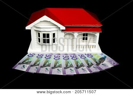 Bungalow villa house model with New Zealand NZ $50 Dollar notes in cash on black background
