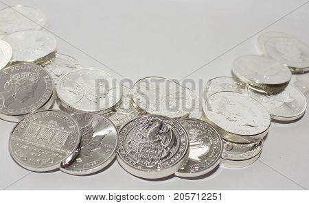 On a gray background are silver coins of an investment silver from an Austrian Canadian and British mints. Vienna Philharmonic Orchestra and Maple Leaf and Dragon of Wales.