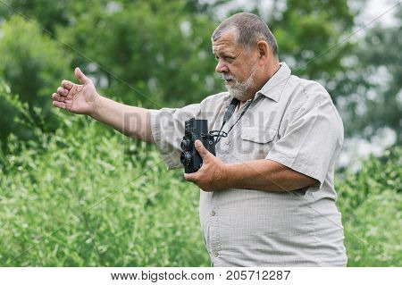 Portrait of a bearded senior photographer man with old camera gesticulating while working outdoor