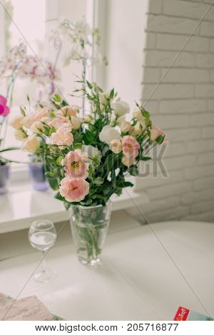 vase with flowers on a table by the window