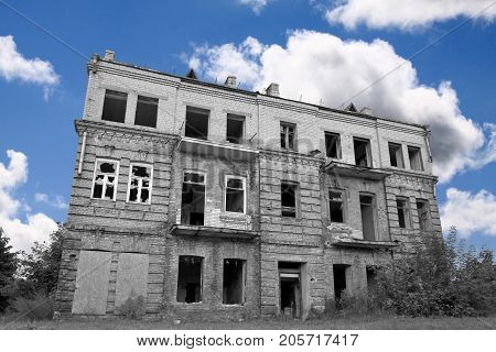 Black and white desaturated abandoned house against colorful blue cloudy sky