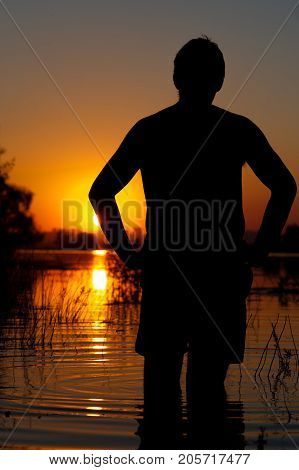 Silhouette of relaxed man enjoying sunset time, standing on river or lake water. Relaxation and leisure concept.