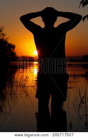 Silhouette of young man enjoying sunset time, watching at river or lake water. Relaxation and leisure concept.