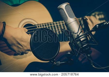 Professional condenser studio microphone over the abstract photo blurred of Closeup musician play the guitar Musical instrument Concept