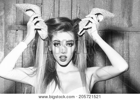 Portrait of surprised glamour fashion young girl with long beautiful hair holding shoes in raised hands near face on wooden background horizontal picture