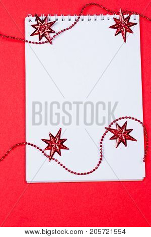 Holiday decorations and notebook on red background