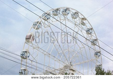 Large ferris wheel is spinning in an amusement park. Fairground ride