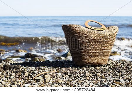 wicker basket bag with accessories for relaxation at sea stands on the coast with pebbles