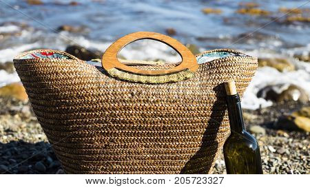 beach bag next to a bottle of red wine on the seashore