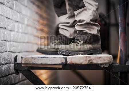 Scaffold Use in Construction Industry Concept Photo. Men Staying on Wood Planks Part of the Scaffolding.