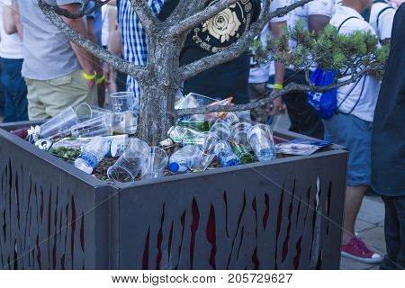 LE MANS, FRANCE - JUNE 16, 2017: Garbage from cans and plastic and paper on the street after the parade of pilots racing in Le mans, France