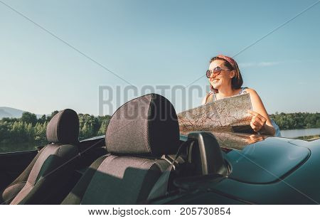 Woman reads a roads map during her auto travel