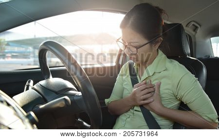 Asian glasses business woman having chest pain from heart attack while driving a car. Illness exhausted disease tired for overtime working concept.