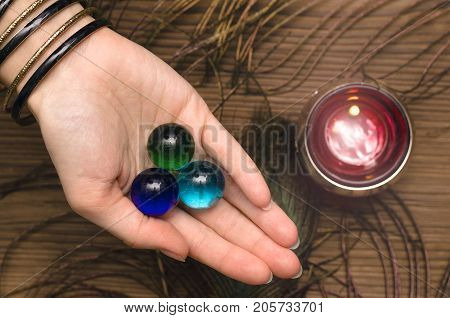 Fortune teller female hands with talisman gems on wooden table and candle. Divination concept.