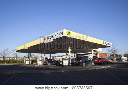 Swansea, UK: December 28, 2016: Customers using the dispensers to fill their cars with petrol at a Morrisons Petrol Station. Morrisons is the fourth largest chain of supermarkets in the United Kingdom