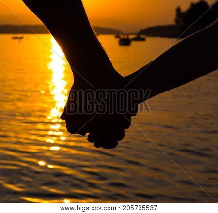 Close up of father and little daughter holding each other hands at the beach