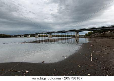 Modern highway bridge over Kamchatka River is largest longest and most flooded river on Kamchatka Peninsula. View of bridge in cloudy weather. Eurasia Russian Far East Kamchatka Region.