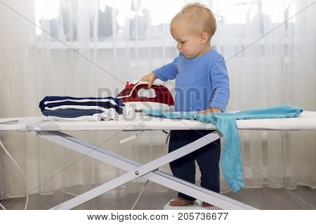 Happy smiling boy ironing clothes. Kid helping with housework. Encouraging Autonomy in children. poster