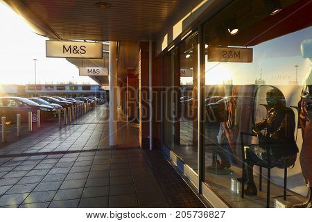 Llanelli, Wales, UK: January 25, 2016: Side view of a Marks and Spencer retail outlet in a small shopping mall. Other named retailers can be seen in the distance.