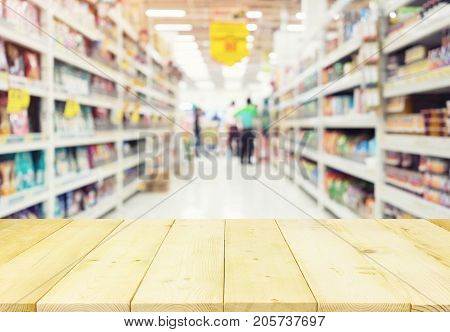 Blurred photo of aisle and products on shelf montage with wood table for shopping background.