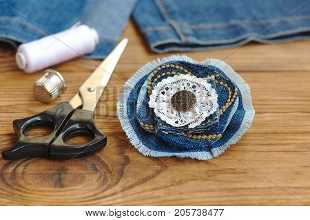 Handmade denim flower jewellery. Scissors, thread, thimble, needle, female old jeans on a wood background. Sewing projects to recycle old jeans. Closeup