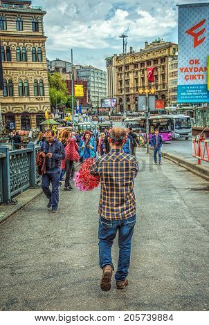ISTANBUL TURKEY - MAY 1 2017: Flower wreath seller walking along the Galata bridge to Beyoglu district and crowds of people