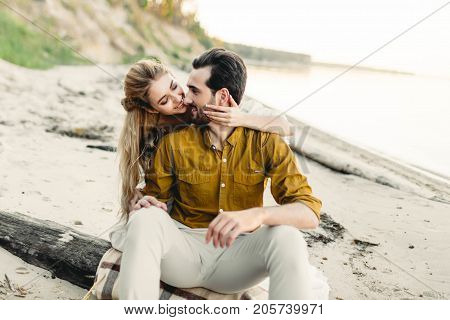 A moment before a kiss. Young couple is having fun and hugging on the beach. A newlyweds looks at each other. Artwork, soft focus