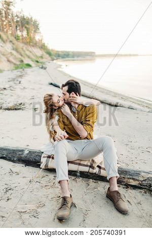 A lovers is kissing. Young couple is having fun and hugging on the beach. Beautiful girl embrace her boyfriend from back. Wedding walk. A newlyweds looks at each other. Artwork, soft focus