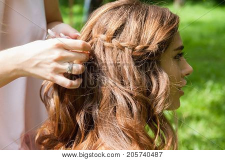 Hairstylist braiding pigtails to young girl outdoor. Creating braids