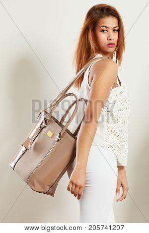 Mulatto Woman Holding Beige Leather Bag.