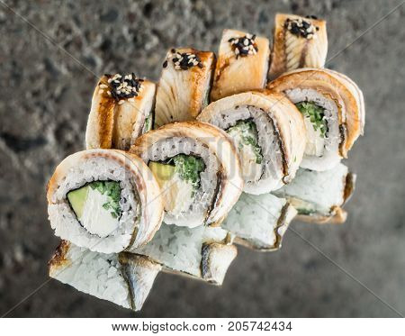Roll with smoked eel, avocado, cucumber and cream cheese over concrete background