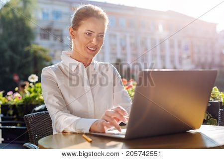 Inspiring ambience. Beautiful young woman sitting on the terrace in cafe and working on the laptop while smiling pleasantly