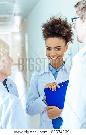 Young african-american medical intern holding a clipboard and smiling