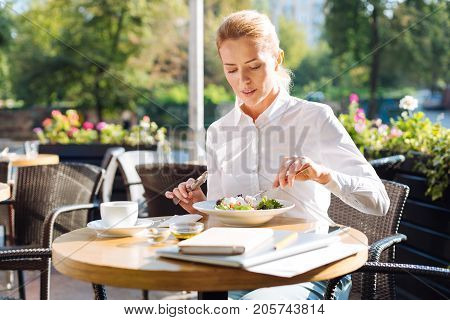 Lunchtime break. Beautiful young woman sitting at the table on the restaurant terrace and eating Greek salad while having a break