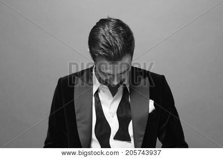 Black and white portrait of a young handsome man in a suit, bow tie and shirt buttons undone, looking down.