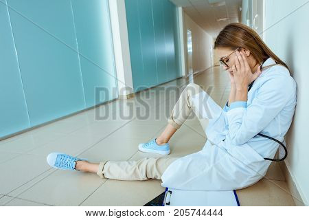 Doctor Sitting In Hospital Corridor
