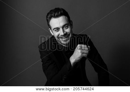 Black and white portrait of a young handsome man in a suit, smiling and looking at the camera, against plain studio background.