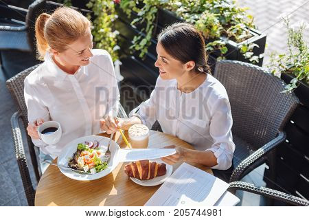 Productive lunchtime. Two lovable young woman sitting at the table in a cafe, having lunch and discussing the data on the printouts