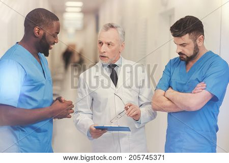 Need your explanation. Attentive mature man standing between his interns and holding glasses in left hand while looking at foreign student