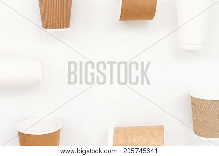 Disposable paper cups on white backgound. Round composition top view.