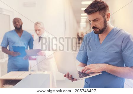 Find information. Attentive young intern bowing head while looking at screen of his gadget and holding computer in right hand