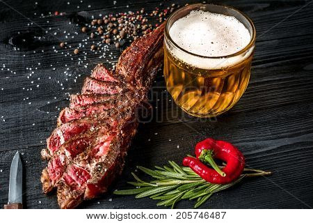 Grilled steak seasoned with spices and fresh herbs served with mug of beer, fresh red pepper. Black wooden background. Still life