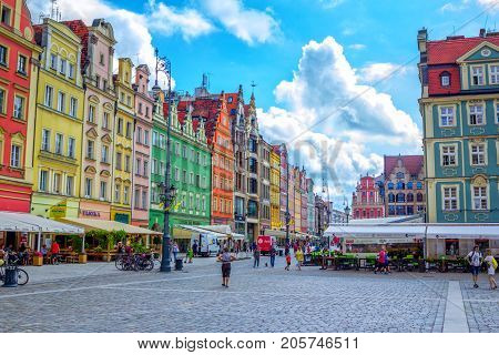 Wroclaw/Poland- August 17, 2017: cityscape of old town Market Square with colorful historical buildings, outdoors restaurants  sunshades, walking tourists and blue sky