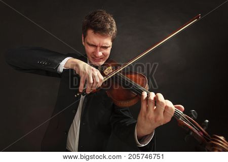 Music passion hobby concept. Man playing violin showing hard emotions and face expressions. Studio shot on dark background
