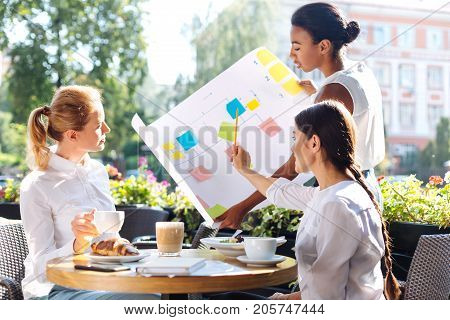 Best cooperation. Pleasant young woman pointing at a sheet with an action algorithm while discussing it with her colleagues during lunch in cafe