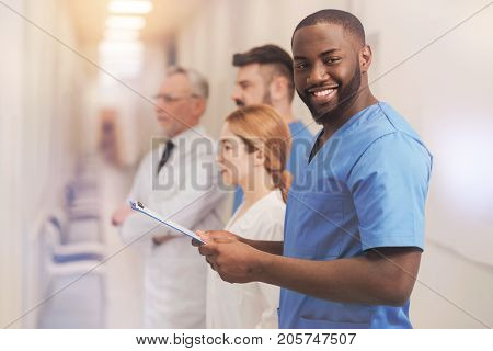 Join us. Positive dark-skinned intern holding folder in both hands and feeling happiness while working in clinic
