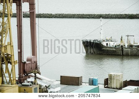 Aerial view of a cargo ship and cranes at industrial port