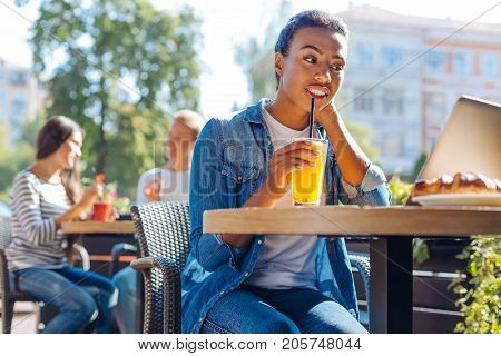 Tasty treat. Pleasant upbeat woman sitting in a cafe, sipping orange juice and watching an episode of her favorite TV-show without headphones