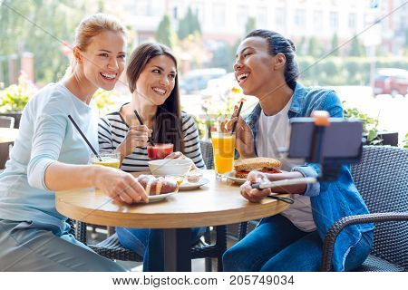 Funny company. Three beautiful female best friends sitting at the table in a cafe and taking a selfie with a monopod while laughing happily