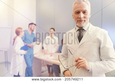 My best group. Handsome grey-haired professor keeping smile on his face and holding glasses in left hand while looking forward
